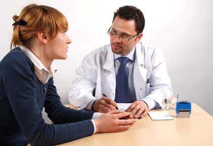 Doctor and young woman patient talking to each other.