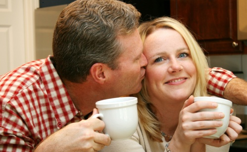 Couple enjoys a hot cup of coffee in the kitchen